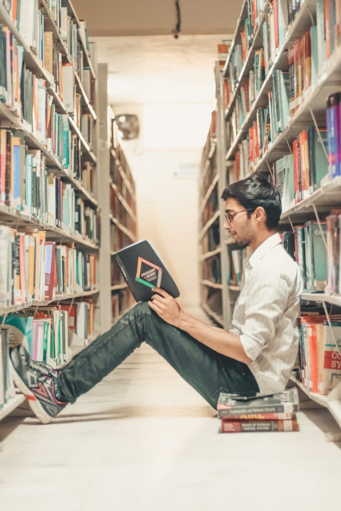 A man studying in a library about study tips